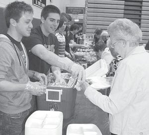 Seth Yoder and Zach Zimmerman, AHS seniors, serve chicken to Doris Rupp, Archbold, during the Senior Citizens Luncheon, Friday, April 26, at Archbold High School. Rupp said she is a 1942 AHS graduate.– photo by David Pugh