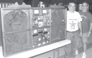 Dave and Doug Fedderke, from left, with the display case containing the uniforms their parents wore during World War II. Their mother, Marcella, whose uniform is on the left, was a member of the Marine Corps. Their father, Maynard, served in the Army. When the parents were discharged, the uniforms were hung in a closet, where they remained for almost 70 years.– photo by David Pugh