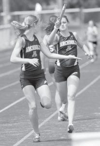 Jensyn Garrow takes the handoff from Tressa Parsley in the girls 4x400 at the Div. III district track and field meet, Saturday, May 25. The Streaks won the race in 4:12.29.– photo by Mary Huber