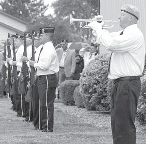 Matt Hines, a member of the Sons of the American Legion, Archbold Squadron 311, plays taps while members of the post rifle squad stand at attention during the Archbold Memorial Day ceremony, Monday, May 27, at the Archbold Knights of Columbus Hall.– photo by David Pugh