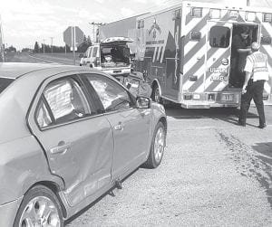 Top: Archbold Rescue prepares to transport a victim of a twocar accident at the intersection of Co. Rds. 19 and C, Wednesday afternoon, May 29. All four persons involved in the crash were treated and released. Above; Fulton County sheriff deputies walk past the wreckage of one of two vehicles involved in a Friday, May 31 crash at the intersection of Co. Rds. F and 20. Two persons were injured; one was transferred to a Toledo hospital.– photos by David Pugh