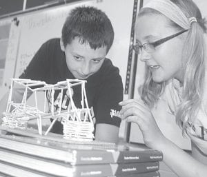 Ian Armstrong, left, and Mauricea Crouch watch as the bridge they and teammate Marais Borton built from balsa wood is tested for strength Thursday, May 30, in Jason Mansfield's fifth grade class at Pettisville. Their structure finally failed under the stress of 6.8 pounds of weight.– photo by David Pugh
