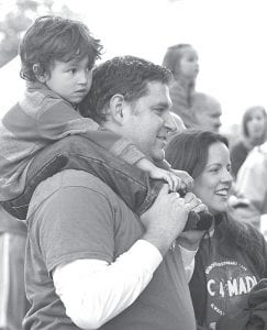 Wil Rodriguez, 4, Maumee, sits on the shoulders of his uncle, Kent Nafziger, Archbold, to watch the Miss Relay contest during the Fulton County Relay For Life event, Friday night, June 7. With them is Wil's aunt, Megan Nafziger.– photo by David Pugh