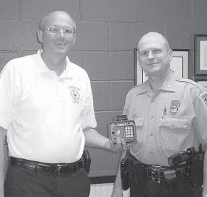 "Andy Brodbeck, Archbold fire chief, and Martin Schmidt, Archbold police chief, with a ""Knox Box."" Boxes placed at homes and businesses allow emergency responders quick access to houses and buildings without having to break open doors. The system has built-in accountability to preserve security.– photo by Andrea Kelly"