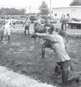 Oozeball, the mud volleyball tournament that is part of the annual Black Swamp Benefit, attracts young competitors from the surrounding area. Above, Malinda Lugbill makes a dive for the ball. Looking on are Grant Rupp, Matt Sevey, Sydney Rupp, Jereme Rupp, and Lexa Richardson. All are from Archbold.– photo by David Pugh