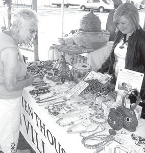 Mary Oyer, left, Wauseon, chats with Britt Wyse, Archbold, in the Ten Thousand Villages tent at the Black Swamp Benefit, Friday and Saturday, June 14-15, at the Fulton County Fairgrounds. photo by David Pugh