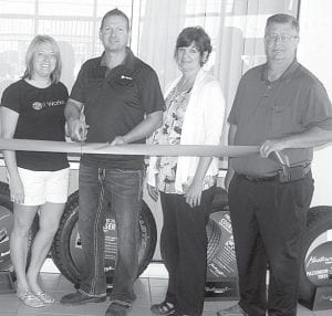 The ribbon was officially cut Friday, June 14, for E&S Tire, which moved into a building at 1910 South Defiance St. The company sells new and used tires, and performs automotive repair. From left: Stacy and Eric Lichtenwald, company owners; Julie Brink, director, Archbold Area Chamber of Commerce; and Dennis Howell, Archbold village administrator.– photo by David Pugh
