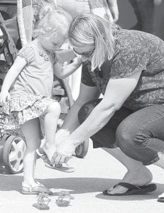 Rebecca Beilke, almost three, Defiance, tries on a pair of shoes at a North Pointe Estates garage sale, Thursday, June 6. Helping is her grandmother, Cindy Baltosser, Archbold. Several families in the North Pointe subdivision hold garage sales on the same day every year.– photo by David Pugh