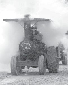 This antique steam tractor was blowing off a huge cloud of steam while waiting in line for the Saturday night, June 29 parade at the annual reunion of the National Threshers Association. Rain fell periodically during the four-day event, held at the Fulton County fairgrounds. While the Saturday parade started under cloudy skies, by the time it was over, a steady, heavy rain was falling.– photo by David Pugh
