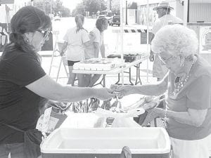 Valerie Kinsman, a vendor at the Archbold Farmers Market, completes a transaction with Lois Lockman, Archbold, Thursday, June 27. It is the fifth year for the downtown market, which has moved from Depot Street to the 100 block of East Holland Street.– photo by David Pugh