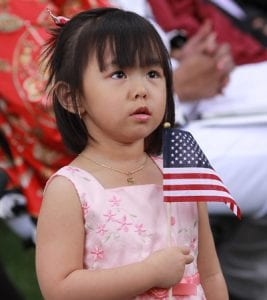 Sydney Nguyen holds a US flag during the ceremony. Her mother, Vui Thi Nguyen, originally from Vietnam now living in Perrysburg, became a US citizen on July 4.