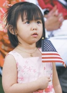 Sydney Nguyen, Perrysburg, waves a US flag as her mother, Vui Thi Nguyen, became an American citizen during a naturalization ceremony at Sauder Village on Independence Day. Forty-six persons from 29 countries were welcomed as new citizens of the US on Thursday, July 4.