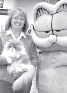 Sabrina Grisier and her Persian cats, which she breeds and shows in competitions throughout Indiana, Ohio, and Michigan. Left: Grisier, with one of her cats, Miss Scarlett Red 'Hara, and another popular feline. Right: Grisier with Miz Behavin' and Whispering Willow, with some of their show ribbons.– courtesy photos