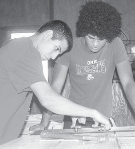 Lukas Rodriguez tightens a bracket on a picnic table while Isaac Burkholder looks on. The two, members of the Archbold High School football team, volunteered to assist the Ridgeville Township Park Board with the picnic table project on Wednesday, July 10.– photo by David Pugh