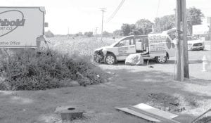 A van driven by Rick Fuller crashed at the intersection of St. Rts. 2 and 66, Tuesday, July 30. The vehicle, which was southbound on St. Rt. 66, went left of center, struck road signs and a large rock, and then hit the sign for Archbold Equipment, finally coming to rest facing east on the other side of the rock, a pole, and a guy-wire. The rock was originally in the bottom right of the photo, next to the knocked-down sign.– photo by Mary Huber