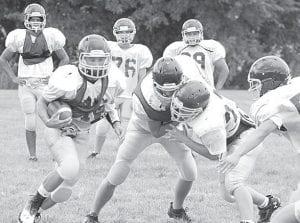 Brandon Goering runs the ball as Skylar Gericke blocks defender Mitchell Hogrefe, Monday, Aug. 5.–photo by David Pugh
