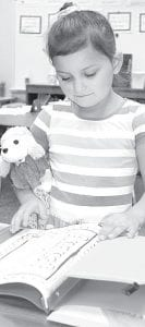 Vannah Rangel looks over a new folder in her kindergarten classroom during the Archbold Elementary School Open House, Monday, Aug. 19. With her is her (stuffed) dog Buttercup, which she said goes with her everywhere.– photo by David Pugh