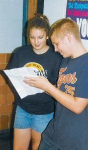Mackenzie Thompson, an Archbold High School sophomore, looks over some paperwork with her brother Adam Armstrong, an eighth grader. The two were visiting Adam's classrooms at Archbold Middle School during open house, Monday night, Aug. 19.– photo by David Pugh