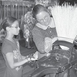 Nancy Lewis, right, a broom shop artisan at Sauder Village, demonstrates the art and craft of broom-making to a guest. Broom-making is just one of several arts and crafts on display at the historic village. Sauder Village will be open through Sunday, Oct. 27.– courtesy photo