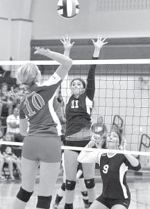 Pettisville's Dana Fricke (11) attempts to block the spike of a Patrick Henry player, Saturday, Aug. 24. Jordyn Pursel (9) times her jump differently.– photo by Mario Gomez