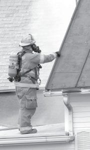 A firefighter in protective clothing combats smoke billowing from a second-story window of a home on Co. Rd. 26-2 that caught fire Tuesday, Aug. 27. Jerry Zimmerman, who lived in the house, suffered serious burns.– photo by Mary Huber