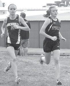 Right: Archbold's Taylor DeWolfe runs side-by-side with Pettisville's Alexa Leppelmeier. Frey won the boys race while Leppelmeier was the girls winner.– photos by Mario Gomez