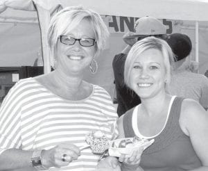Cheryl Nofziger, Pettisville, and her daughter Ambria enjoy caramel apples.– photo by Mary Huber