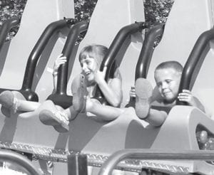 Five-year-old twins Evynn and Avery Roth, Archbold, from left, ride the Mega Bounce.– photo by Mary Huber
