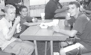 Tug Robison, an Archbold seventh grader, and Corbin Vonier and Logan Roth, eighth graders, from left, take a break with some ice cream.– photo by Mary Huber