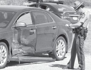 An Ohio State Highway Patrol trooper fills out a report following a two-vehicle collision on St. Rt. 66 that occurred Thursday, Sept. 5, at 1:08 pm. The drivers of the two autos were taken to the Fulton County Health Center, where they were treated and released.– photo by David Pugh