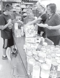 Archbold sixth grade students, with their teacher Lori Luderman, far right, count food items they collected as part of 9-11 day, a national day of service on the anniversary of the Sept. 11, 2001 terrorist attacks. Students, from left: Brooks Behnfeldt, Elijah Zimmerman, Chloe Nofziger, and Katie Goehring.– photo by David Pugh