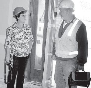 Nanette Buehrer, left, director of development and community services for the Fairlawn Retirement Community, talks with a construction worker at the front door of the Rupp Rehabilitation Neighborhood. The 12-bed, $5.5-million addition to Fairlawn will accommodate persons who need to recover from illness, injury, or surgical procedures.– photo by David Pugh