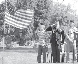 Above, from left: Jaton Roehl, a Pettisville sixth grade student, and Danny Dymarkowski, former U.S. Army sergeant, salute the flag while Daniel Sauder, a PHS '14 graduate, looks on during the Pettisville Memorial Day Ceremony in the Pettisville cemetery. Below: Children from Ridgeville wait to go on stage in the annual children's flag drill during the Ridgeville Corners ceremony at the Ridgeville Corners American Legion Hall.–top photo by David Pugh; bottom photo courtesy V. Hesterman