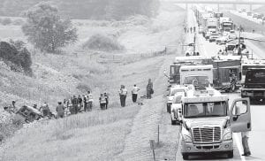 Rescue personnel from Archbold, Wauseon, and Fayette tend to the five victims of a Friday afternoon, Aug. 1 crash on the Ohio Turnpike that occurred when a van, in the ditch at left, went out of control and overturned. Behind the rescue vehicles are two medical helicopters, waiting to fly three victims to Toledo Hospital. Also note the line of stopped semis, waiting for the eastbound lanes to reopen. The eastbound lanes were closed for about 90 minutes.– photo by David Pugh