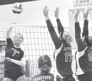 Cassidy Williams spikes the volleyball past a pair of Crestview defenders, Saturday, Aug. 23.– photo by Mario Gomez