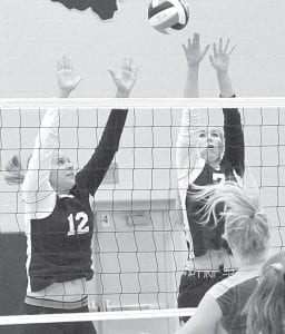 Kate Kauffman, left, and Amber Klopfenstein try to block a Holgate spike, Thursday, Aug. 21. The Birds won the match in three games.– photo by Mario Gomez