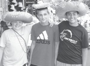 Shane Eicher, 12; Gavin Seiler, 13; and Juan Garcia, 13, wear the doughnuts they won playing midway games at the fair. They are all Archbold seventh graders.– photo by Mary Huber