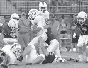 Archbold's Jacob Rodriguez (58) and Justin Lovejoy (75) tackle a Delta Panther in the first quarter of their NWOAL opener, Friday, Sept. 5. The game was postponed with 10 seconds left in the first quarter after a storm rolled in. After play resumed Saturday, Sept. 6, the Panthers rolled to a 42-7 victory.– photo by Mario Gomez