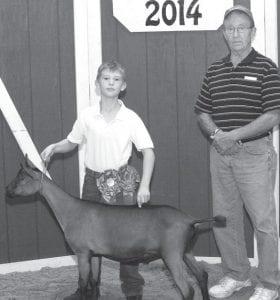 Grand champion market dairy goat exhibitor Paige Holdridge, daughter of Gabe & Mollie, Delta, represented by Layne Holdridge (left). Buyer: Beaverson Machine, represented by Ralph Beaverson.