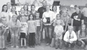 Horse item, which benefits over 100 youth in 4-H horse projects. Pictured with Fulton County 4-H horse exhibitors is buyer Machacek Concrete, represented by Shawn Machacek (rear center) and Adrianna Hibbard (center, holding plaque), the 2014 4-H Horse Queen, daughter of Trevor & Lynnette, Fayette.