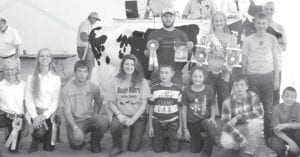 Grand champion dairy cow exhibitor Austin Krieger, rear far right, son of Shawn & Kim, Wauseon. Buyer: Fulton County Dairy Association, represented by Greg Clapp (center). Also pictured are the 2014 Jr. Dairy Ambassador, Courtney Krieger, daughter of Shawn & Kim and Dairy youth Mason Henricks, right of Dairy Ambassador. Kneeling, from left: Anneli Shaw, Jensi Shaw, Trent Schroeder, Emalee Stewart, Ethan Glover, Aaliyah Glover, Trey Schroeder, Logan Henricks.
