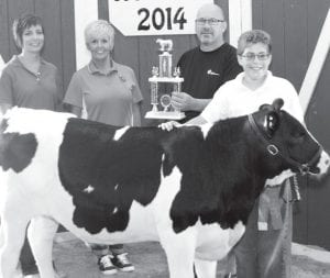 Grand champion dairy feeder calf exhibitor Cole Riches, son of Carrie Price, Delta, and Ryan Riches, Wauseon. Buyers, from left: Farmers & Merchants State Bank, represented by Jennifer Knapp and Debra Kauffman; Gerald Grain Center, represented by Randy Heldman.