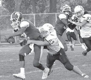 Blue Streak Mitchell Hogrefe (63) tackles Spartan quarterback Brandon Winters.– photo by Mario Gomez