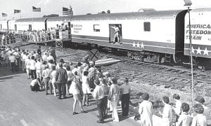 """This photo shows people waiting in line to go through the American Freedom Train exhibit. More than 36,600 people went through the exhibit; some waited as long as six hours to board the train, which visited Archbold for three days in 1975. The train is parked on a """"spur"""" track along Myers Road, south of West Barre Road. Today, the Sauder Woodworking Myers Road plant stands behind the railroad spur.– photo from Archbold Buckeye archives"""