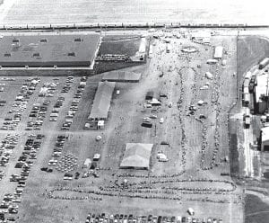 This aerial view shows the line of people waiting to tour the American Freedom Train exhibition. Despite high temperatures and heavy rain, it was estimated that as many as 50,000 people visited Archbold over the three days the train was in Archbold. Note how the line coils back and forth. Tents along the way offered local exhibits ranging from local quilters to a car driven by racer John Huffman.– photo from Archbold Buckeye archives