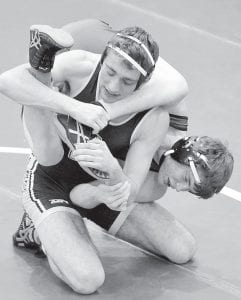 Garrett Grime tries to score on a leg attack for a takedown of Swanton's Tyler Houston in the NWOAL championship semifinals.– photo by Mario Gomez