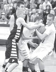Left: Pettisville's Landon Roth, left, fights for control of the ball with a pair of Stryker Panthers. Right: Evan King was 3-3 at the foul line against Stryker.– photos by Mario Gomez