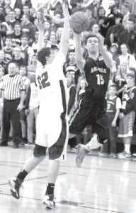Archbold's Austin Welch streaks past Elmwood's Trevor Solether in their Division III sectional championship game. AHS advanced to tomorrow's district semfiinal against Van Buren with a 65-58 victory.– photo by Scott Schultz