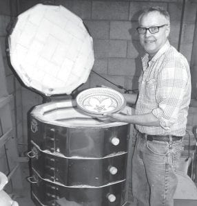 Mark Nafziger, potter at Sauder Village, removes a bowl from the kiln, one of the thousands of clay pottery pieces he hand makes. This year, he is creating a special plate commemorating the 50th anniversary of the Fairlawn Haven Auxiliary Auction. With the April 8 auction date approaching, he jokingly said the special plate may still be warm from the kiln when he delivers it.– photo by David Pugh