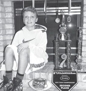 D.J. Newman, 12, Archbold, with some of the trophies and awards he received in sports competitions since the age of 9. This year, he is the co-champion free-throw shooter among Ohio 12-year-olds. His parents are Doug and Roxy.– photo by David Pugh